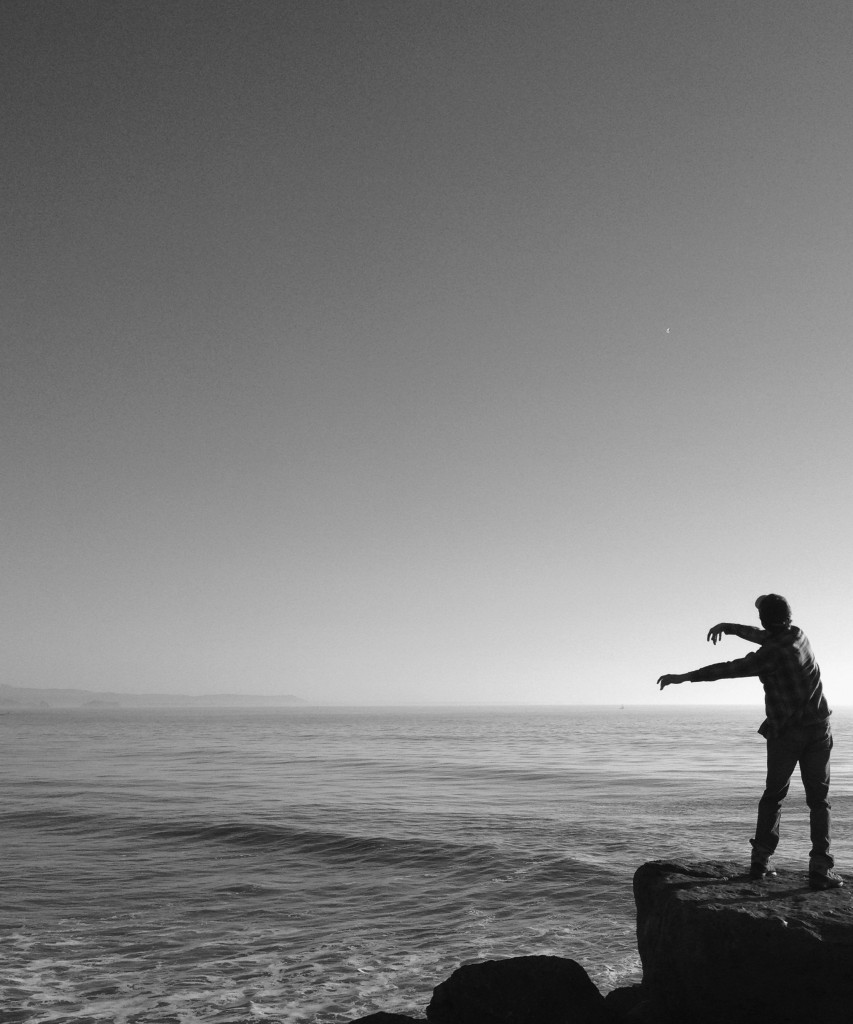 My son tossing a crystal into the sea.
